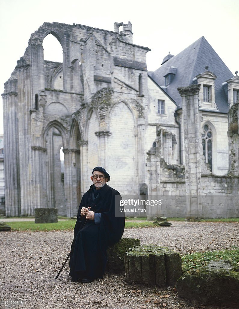 Abbe Pierre staying at the Benedictine Abbey of St. Wandrille near Caudebec-en-Caux plan opposite the abbe seated before asking the nave and north transept in ruins.