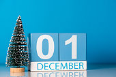 December 1st. Day 1 of december month, calendar with little christmas tree on blue background. Winter time. New year concept.