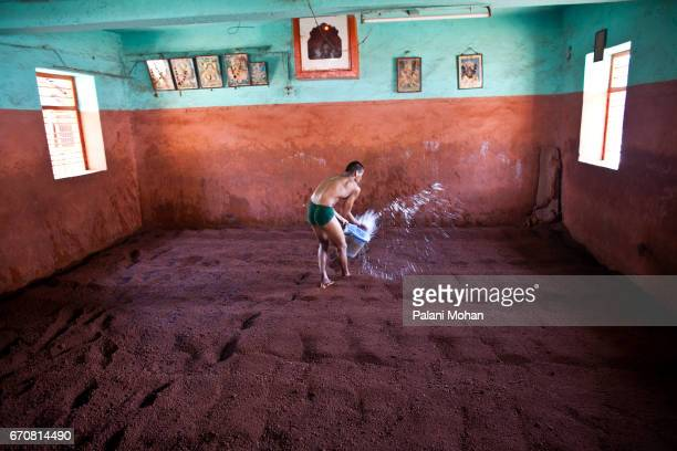 A young Kushti wrestler throws water on the red clay surface before the start of a training session at a Akhada or wrestling schools in the town of...