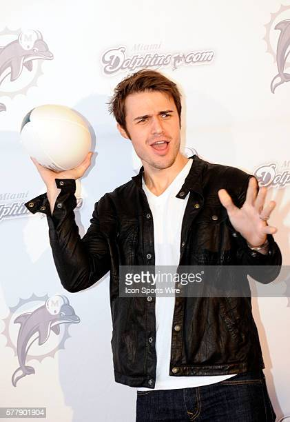 American Idol winner Kris Allen poses with a football on the the orange carpet before the start of the NFL game between the Cleveland Browns and the...
