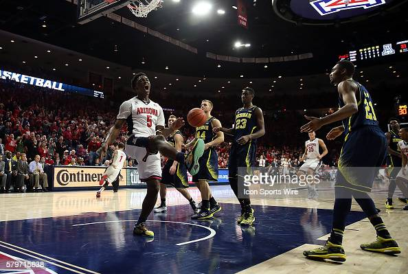 Arizona Wildcats forward Stanley Johnson celebrates a dunk over Michigan Wolverines guard Spike Albrecht and forward Max Bielfeldt during the first...