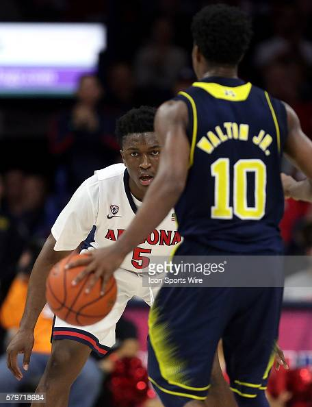 Arizona Wildcats forward Stanley Johnson defends Michigan Wolverines guard Derrick Walton Jr #10 during the first half of the college basketball game...