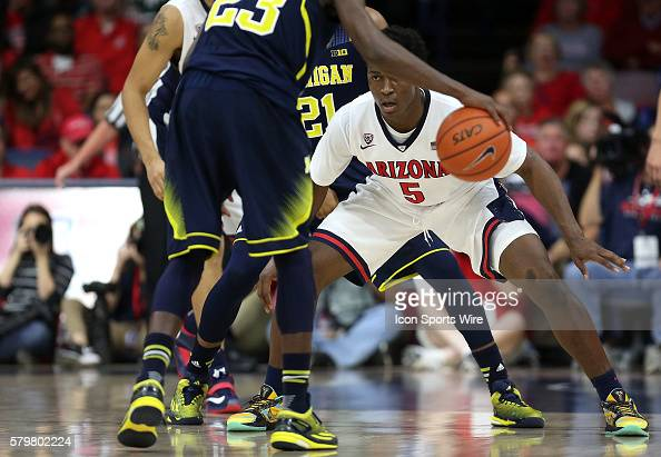 Arizona Wildcats forward Stanley Johnson guards Michigan Wolverines guard Caris LeVert during the first half of the college basketball game between...