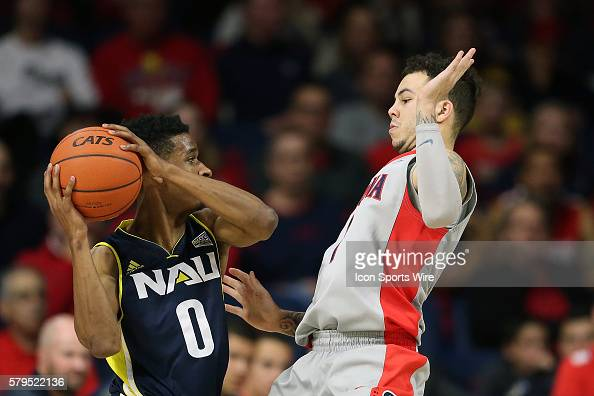 Northern Arizona Lumberjacks guard Torry Johnson is defended by Arizona Wildcats guard Gabe York during the first half of college basketball game at...