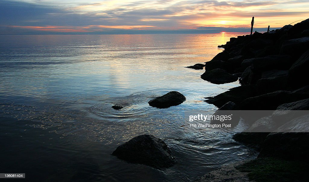 Water swirls around the rocks of a breakwater as the sun rises over the Chesapeake Bay on the the first morning of astronomical winter, the Winter Solstice, in North Beach, MD, December 22, 2011.