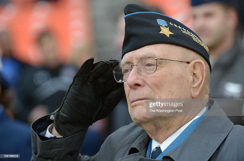 Medal of Honor Recipient Hershal 'Woody' Williams, who achieved his recognition for his actions in the battle for Iwo Jima, saluts during the playing of the National Anthem prior to the Military Bowl on December 27, 2012 in Washington, DC