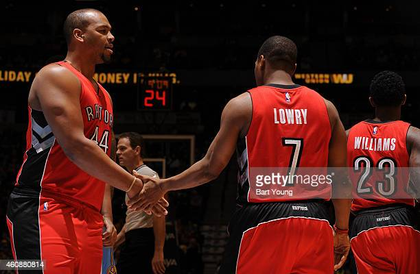 Kyle Lowry high fives teammate Chuck Hayes of the Toronto Raptorsduring the game on December 28 2014 at Pepsi Center in Denver Colorado NOTE TO USER...