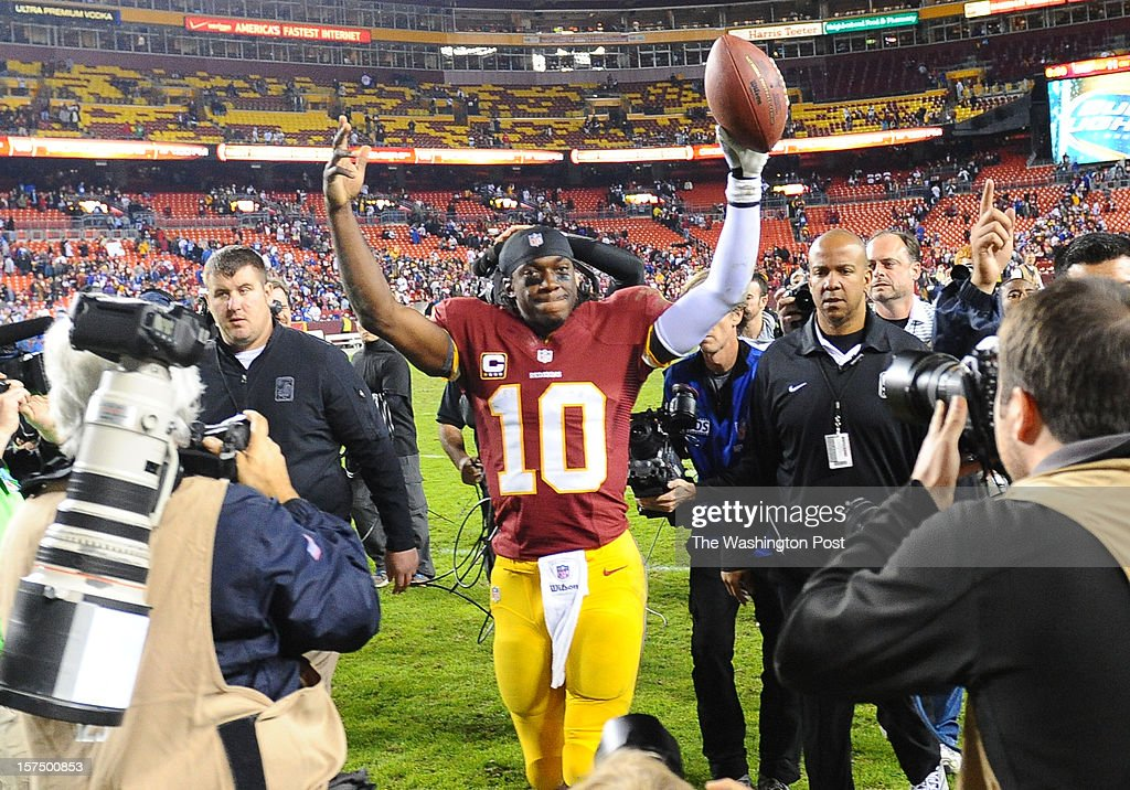 Washington Redskins quarterback Robert Griffin III (10) hoists the game ball after their 17-16 win over the New York Giants at FedEx field on December 3, 2012 in Landover, MD
