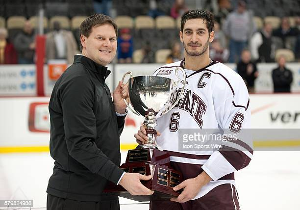 Colgate Raiders defensemen Spiro Goulakos is handed the Confluence Cup by Pittsburgh Penguins Assistant General Manager Jason Botterill after...