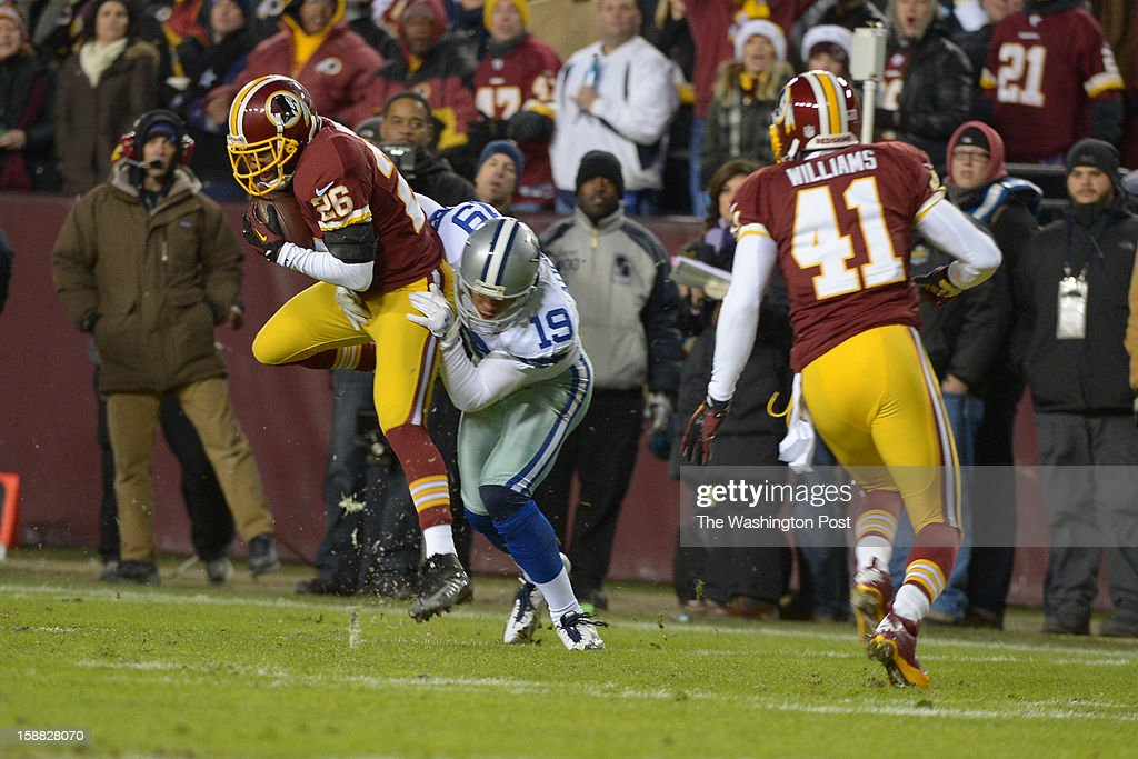 Washington Redskins cornerback Josh Wilson (26) intercepts a pass from Dallas Cowboys quarterback Tony Romo (9) intended for Dallas Cowboys wide receiver Miles Austin (19) who tackles Wilson at FedEx field on December 30, 2012 in Landover, MD