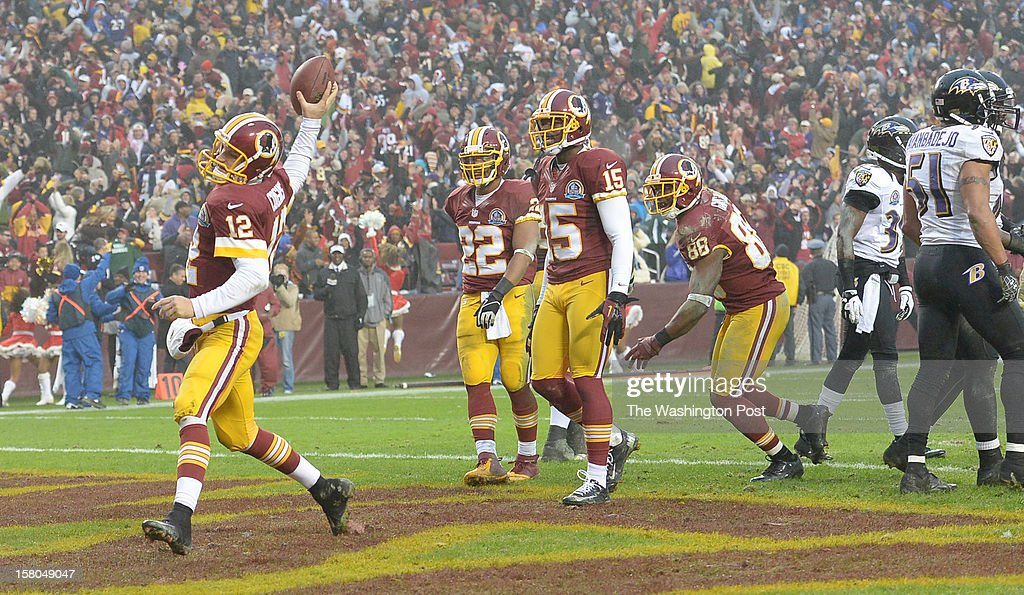 Washington Redskins quarterback Kirk Cousins (12) spikes the ball following his two point conversion to tie the game against the Baltimore Ravens at FedEx Field on December 9, 2012 in Landover, MD
