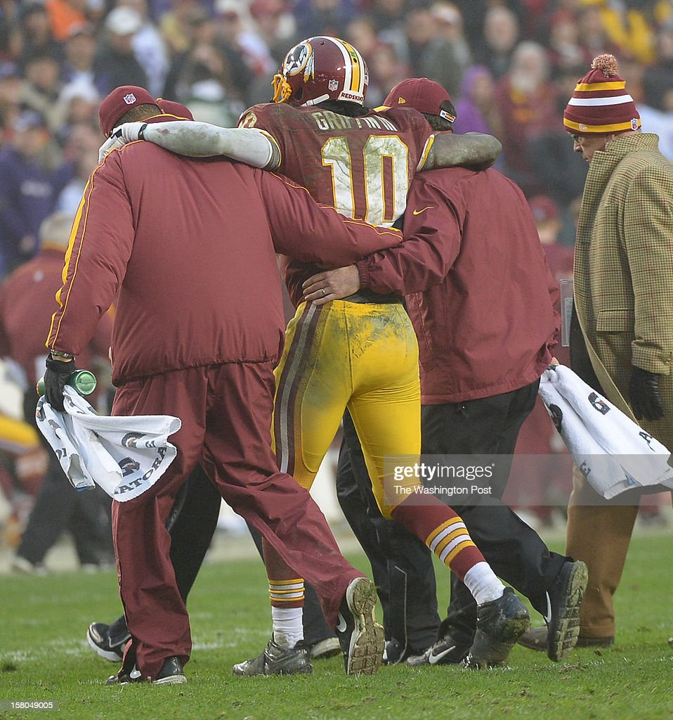 Washington Redskins quarterback Robert Griffin III (10) is helped from the field in the 4th quarter after suffering an injury at FedEx Field on December 9, 2012 in Landover, MD