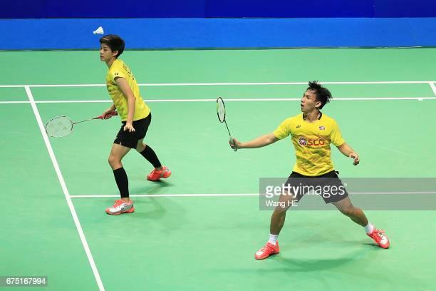 Dechapol Puavaranukroh of Thailand hits a return next to him partner Sapsiree Taerattanachai during their mixed doubles final match against Lu Kai...