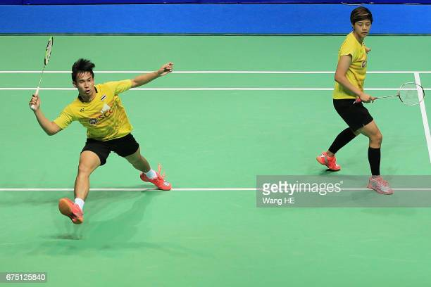 Dechapol Puavaranukroh of Thailand hits a return next to his partner Sapslewiree Taerattan during their mixed doubles final match against Lu Kai and...