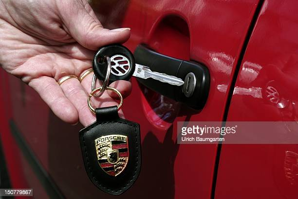 GERMANY BONN Decision VW Porsche Our picture shows a hand holding a car key of VW Volkswagen with a Porsche coat of arms as a key fob into a car door...