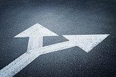A bi-directional arrow symbol on an asphalt road for the concept of choice