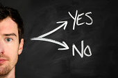 Male against blackboard with decisions to make