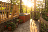 Gorgeous landscaped wooden deck with sun shining through trees of surrounding forest into mist of hot tub. Potted flowers surround tub.