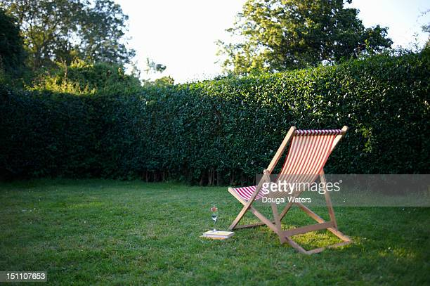 Deck chair and drink in garden.