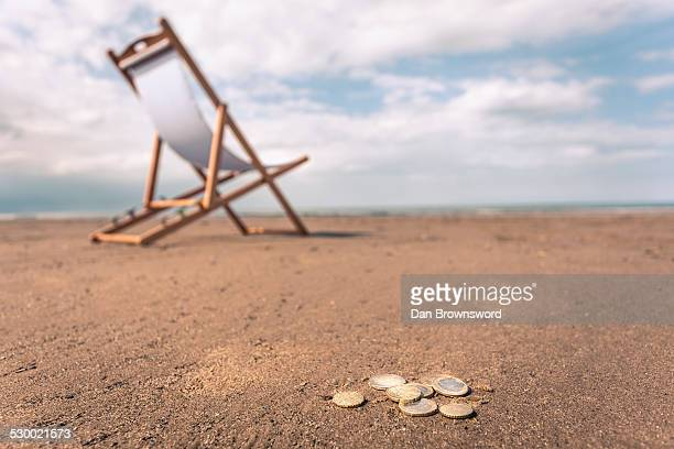 Deck chair on beach, coins on sand in foreground