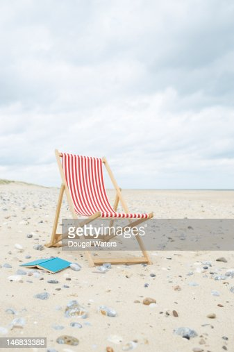 Deck chair with book on sand at beach.