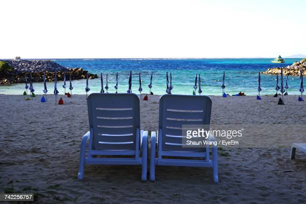 Deck Chairs And Parasols At Beach Against Clear Sky