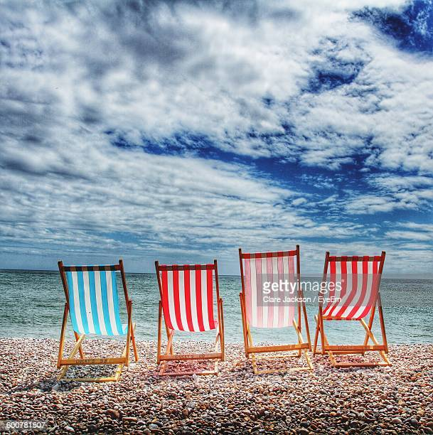 Deck Chairs At Sea Shore Against Cloudy Sky