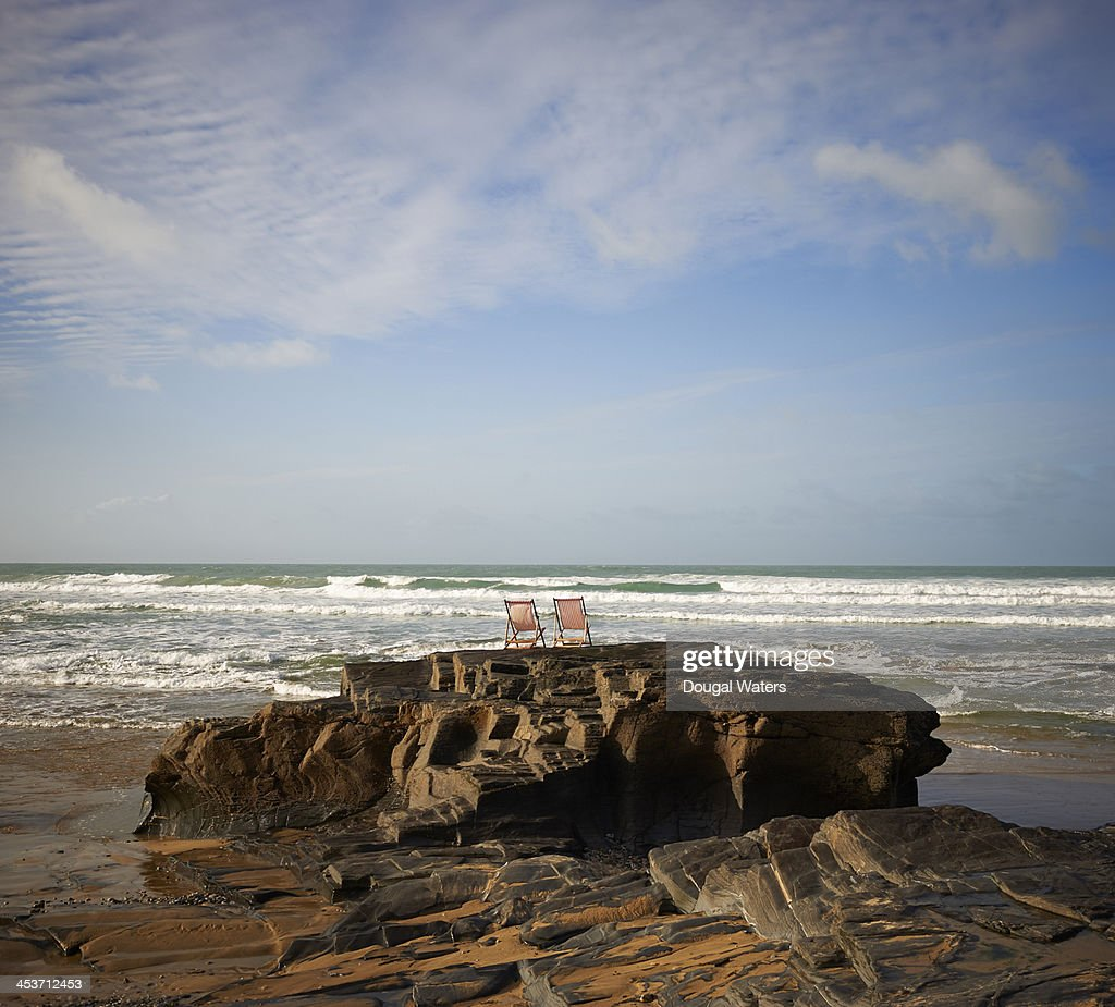 Deck chairs on coastal rock looking out to sea. : Foto de stock