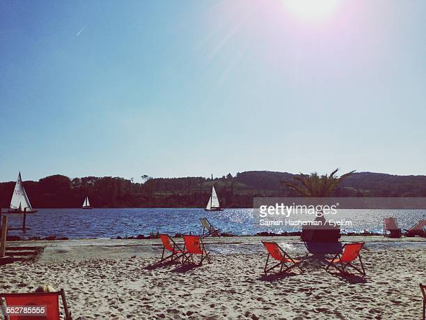 Deck Chairs On Sandy River Shore