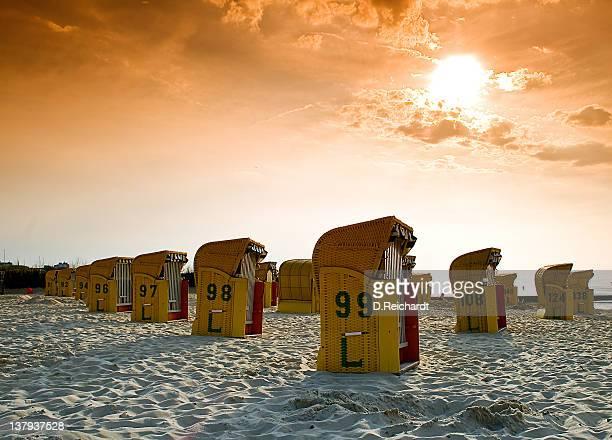 Deckchairs on beach during sunset