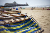 'Folded pile of deckchairs on the promenade in Bournemouth, UK. Shallow focus with pier in background'