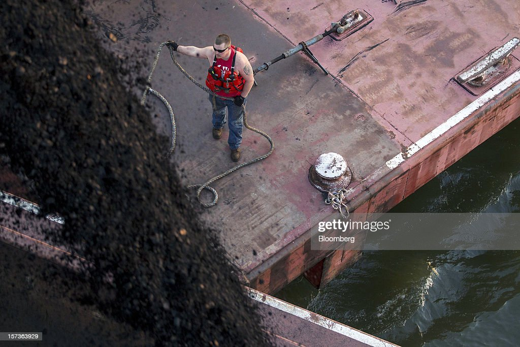 Deckhand Josh Rosendohl works on a barge as another is filled with coal on the Mississippi River at Knight Hawk Coal LLC in Chester, Illinois, U.S., on Friday, Nov. 30, 2012. The family-owned Knight Hawk employs 400 people and has another 300 contractors, including about 140 truck drivers. The company has never had layoffs since it opened in 1998, said Andrew Carter, vice president of sales and distribution. A blocked Mississippi could change that. Photographer: Whitney Curtis/Bloomberg via Getty Images