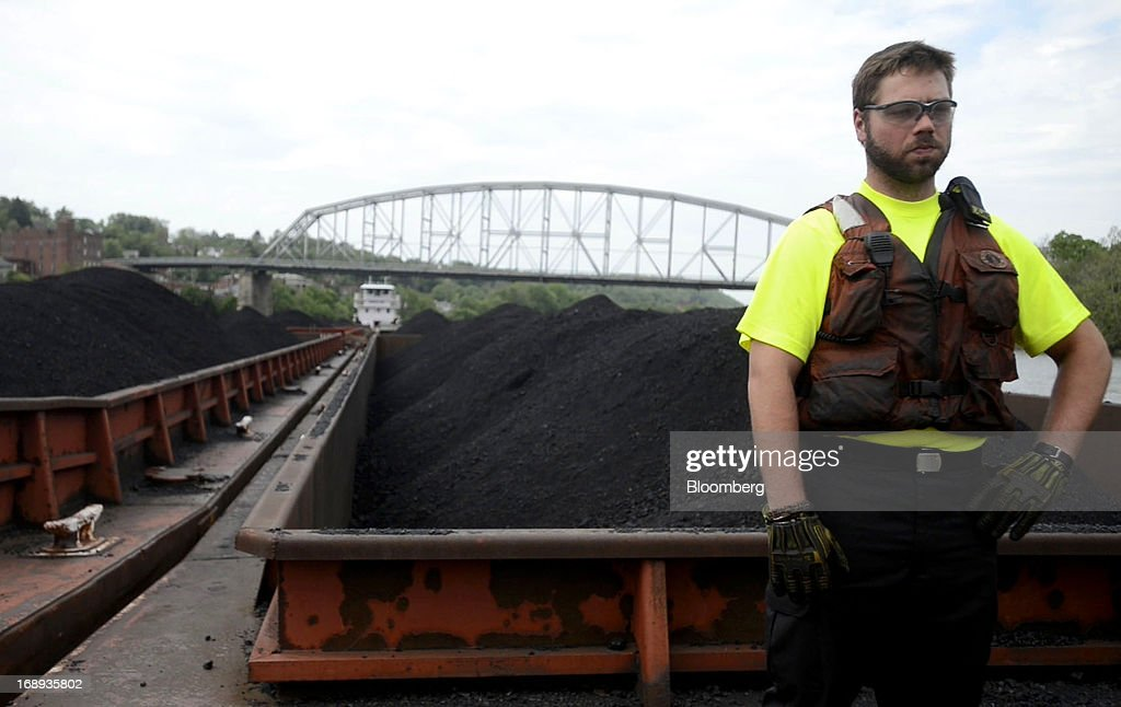 A deckhand stands in the front of jumbo barges, containing coal, during transport along the Monongahela River by Consol Energy's Champion Coal tow boat outside of Pittsburgh, Pennsylvania, U.S., on Wednesday, May 15, 2013. Coal's prospects are improving after its share of U.S. power generation fell last year to 34 percent, the lowest since at least 1973, Energy Department data show. Hotter temperatures this summer that prompt American households to use more air conditioning will boost demand for coal and the railroads that ship it. Photographer: Ty Wright/Bloomberg via Getty Images