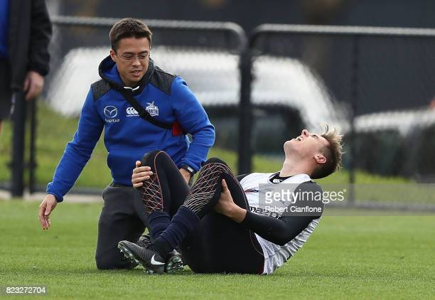 Declan Watson of the Kangaroos appears injured during a North Melbourne Kangaroos AFL training session at Arden Street Ground on July 27 2017 in...