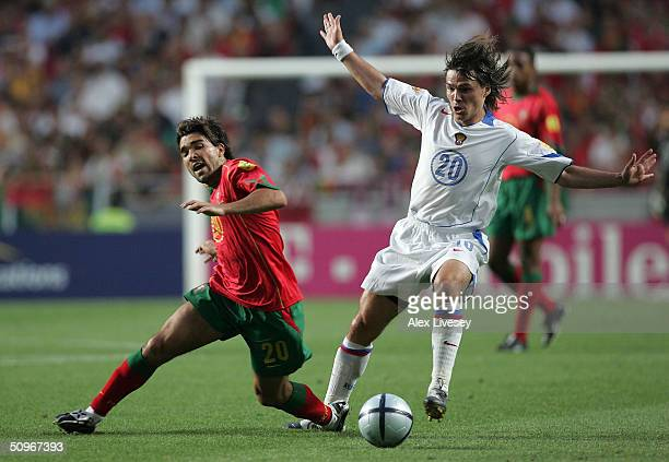 Deco of Portugal clashes with Dmitry Loskov of Russia during the UEFA Euro 2004 Group A match between Russia and Portugal at the Luz Stadium on June...