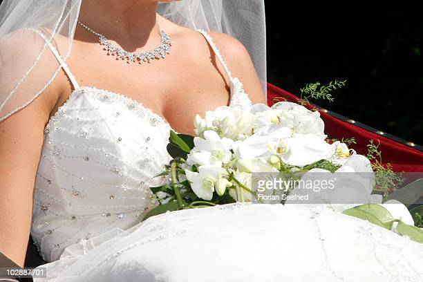 Decolletage jewellery and bridal bouquet of Claudia Schattenberg is pictured after her church wedding with Philipp Lahm at the Sankt Emmerans Chruch...