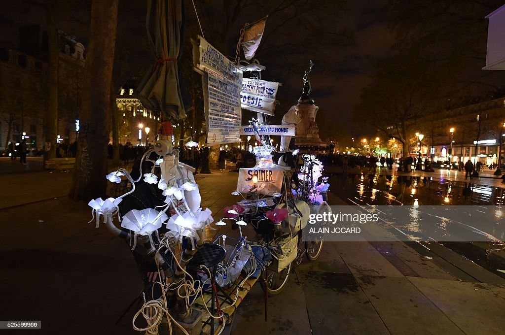 A decorated bicycle with slogans reading 'Change for all, Poetry, Create a new world, Love each other' is pictured on Place de la Republique attend the Nuit Debout, or 'Up All Night' movement on April 28, 2016 in Paris. The 'Nuit Debout' demonstrations began on March 31 in opposition to the government's proposed labour reforms.
