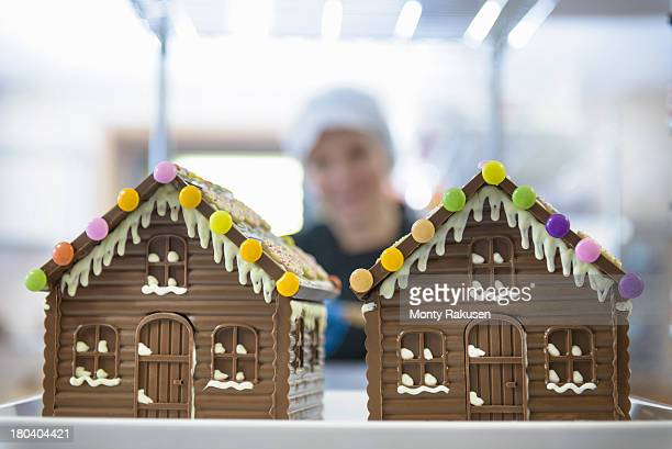 Decorated chocolate houses on shelf in chocolate factory with chocolatier in background
