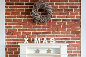 Decorated Christmas fireplace on a brick wall in a rustic home decorated with a wreath of twigs, stocking, stars and the letters Xmas to celebrate the holiday season