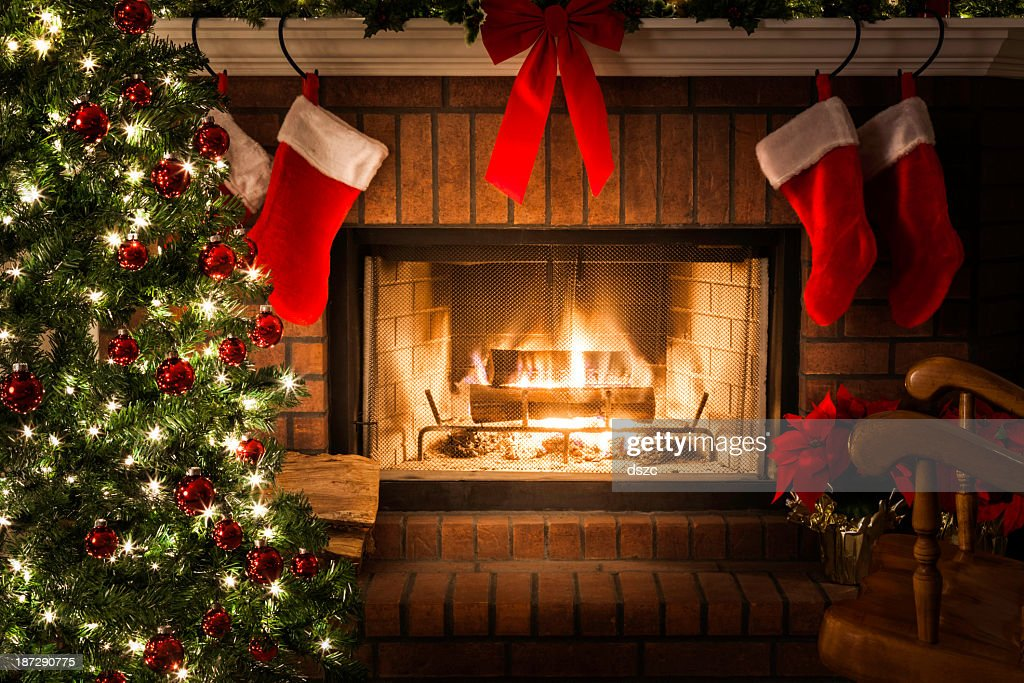 Decorated christmas tree blazing fire in fireplace