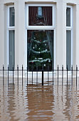 A decorated Christmas tree sits in the window of a stricken home as Storm Desmond causes flooding on December 6 2015 in Carlisle England Storm...