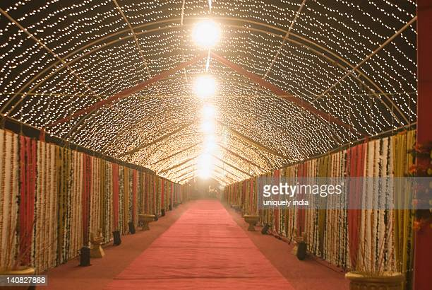 Decorated corridor of a wedding tent lit up at night
