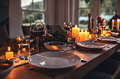 Close up shot of christmas festive table with no people. Dining table with plates, wine glasses and candles.