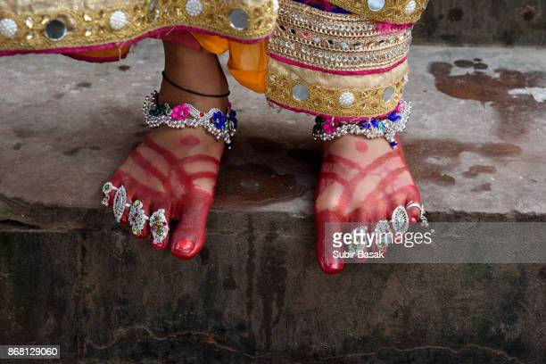 Decorated feet of an Indian woman with bangle and traditional ornaments.