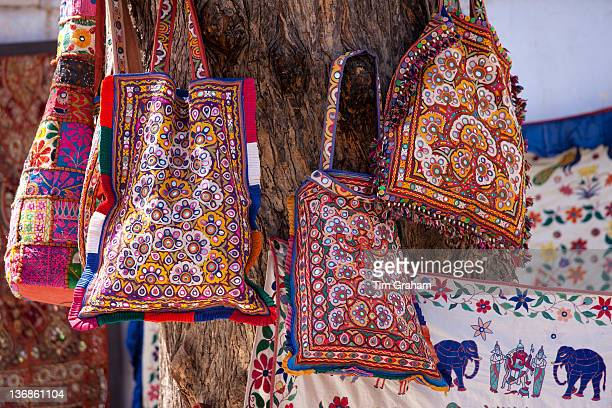 Decorated handbags on sale hanging from tree in street market in City Palace Road Udaipur Rajasthan Western India