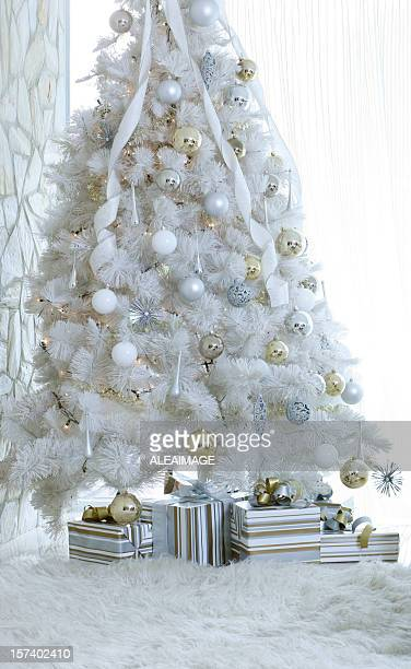 Decorated white Christmas tree with snow and presents below