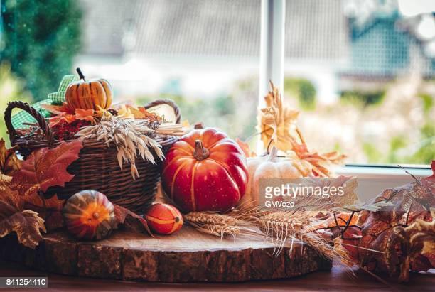 Ventana decorada con calabazas, hojas y frutos secos