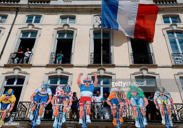 Decorations representing cyclists wearing leaders jerseys displayed on the facade of a building are pictured with a French flag prior to the...