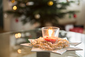 Decorative candle in glass holder with pearl necklaces in front of Christmas tree, Bavaria, Germany
