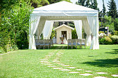Decorative place for ceremonies or entertainments. Outdoor reception under tents and trees
